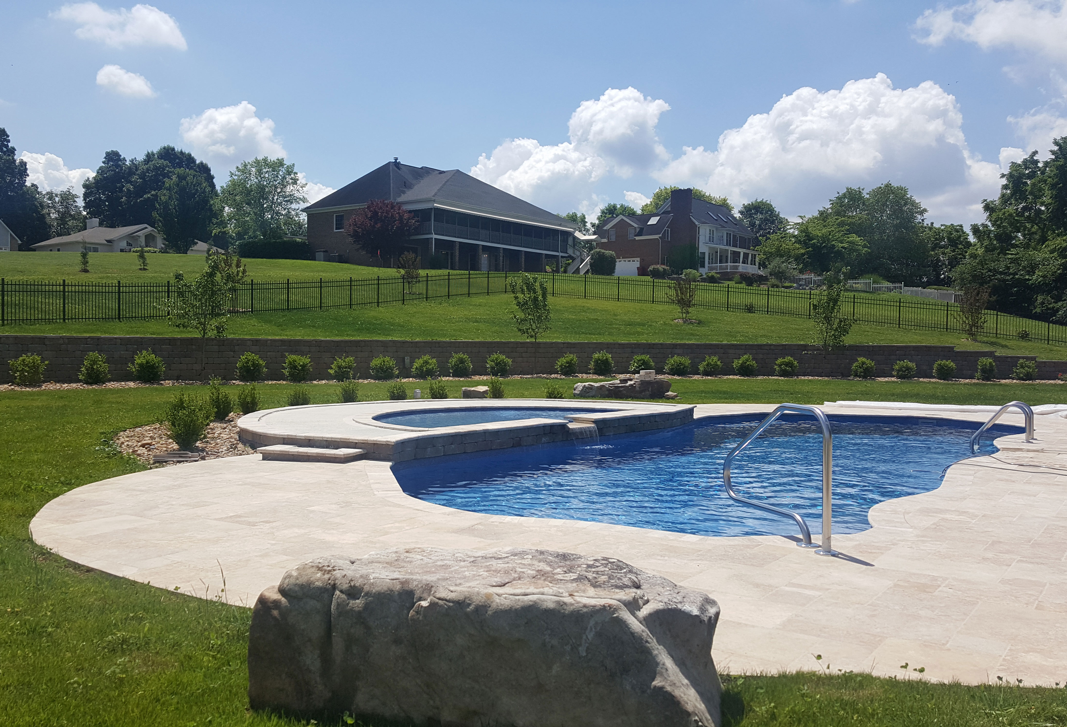 Grand Home Overlooking Large In Ground Pool With Tanning Ledge and Boulders