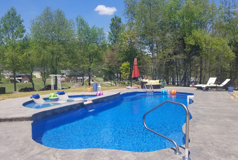 Fiberglass swimming pool with tanning ledge including submerged lounge chairs