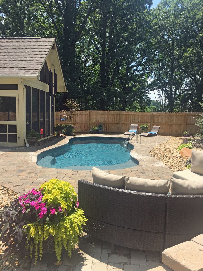 Private backyard oasis with lush planters, screened porch, extensive hardscaping and modern outdoor furniture