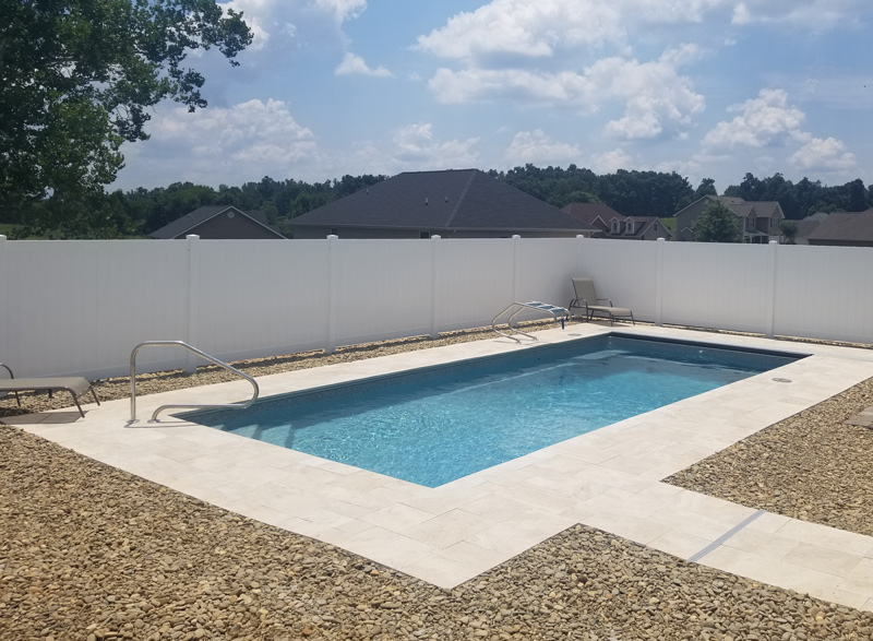 Liner pool with entry stairs in small backyard in subdivision