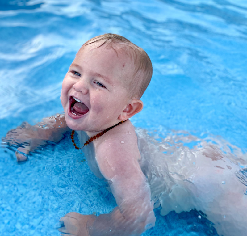 Infant swimming in shallow tanning ledge feature of swimming pool.