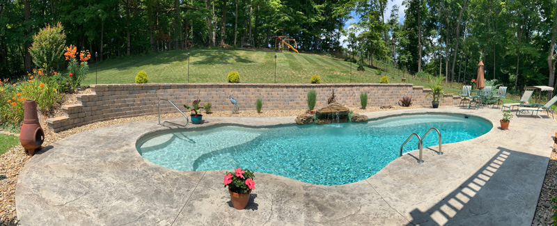 Fiberglass pool with waterfall feature by retaining wall with hilly yard