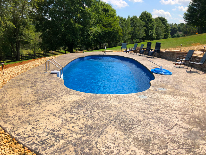 Large fiberglass pool on a big sloping lot with mature trees out in the countryside