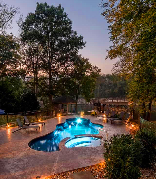Fiberglass pool with integrated lighting glowing blue at night alongside Holston Lake in Tennessee