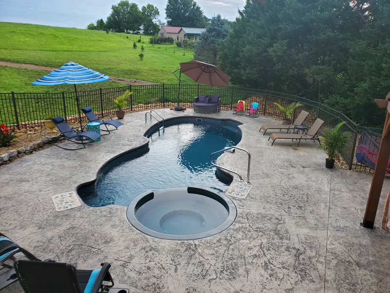A fun fiberglass pool with integrated jetted jot tub next to a hay field
