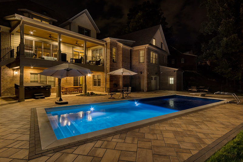 A well lit backyard at night with large tiled area and illuminated swimming pool with auto cover deploying