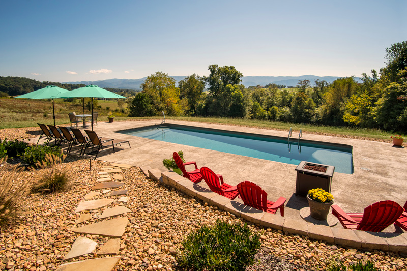 A swimming pool with lounge chairs overlooking the Blue Ridge Mountains in Parrottsville, TN
