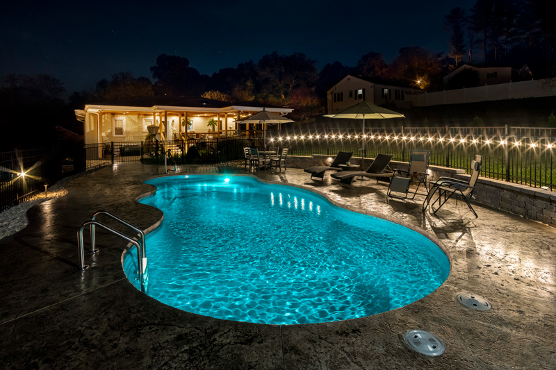 Bright blue pool water at night with cool landscape lighting in Johnson City, TN
