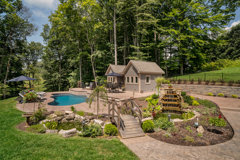 A charming backyard oasis with charming landscaping including waterfall, ponds, footbridge, water plants.... and of course a swimming pool and deluxe cabana