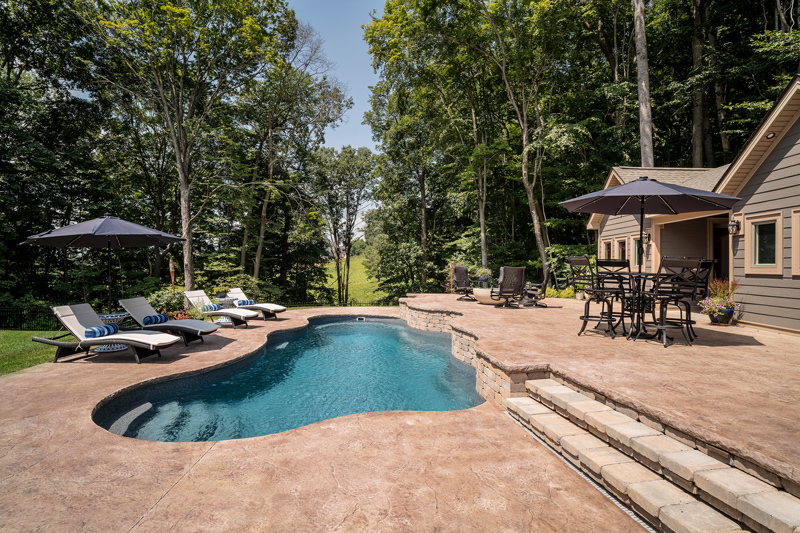 This inground fiberglass lagoon pool with integrated stair entry radiates a refreshing calm alongside the forest edge