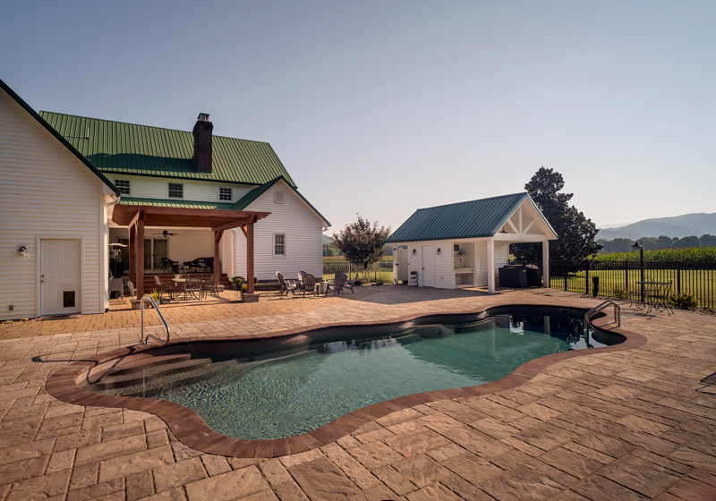 Expansive and interesting paver decking surrounds this fiberglass pool with Tennessee mountains in the background