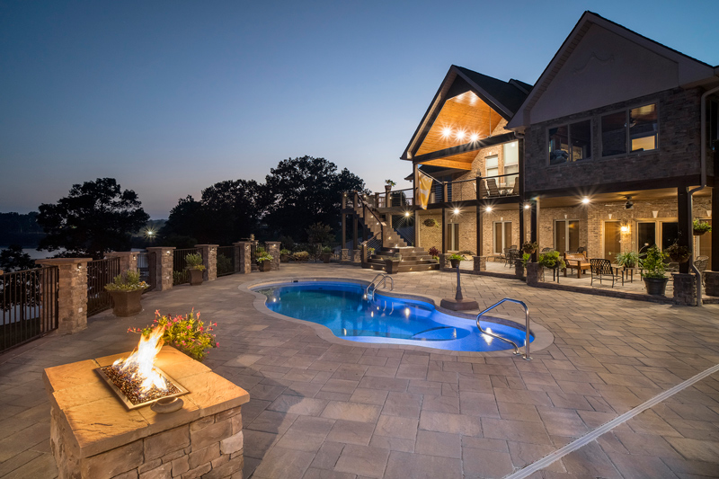 Night time shot of illuminated pool with fire features overlooking the lake at dusk in Morristown, TN